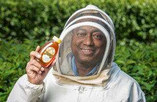 Anthony Dickerson poses inside the beekeeping fit with a jar of their own honey.